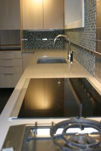 Stainless plugmold strips set into recycled glass tile backsplash